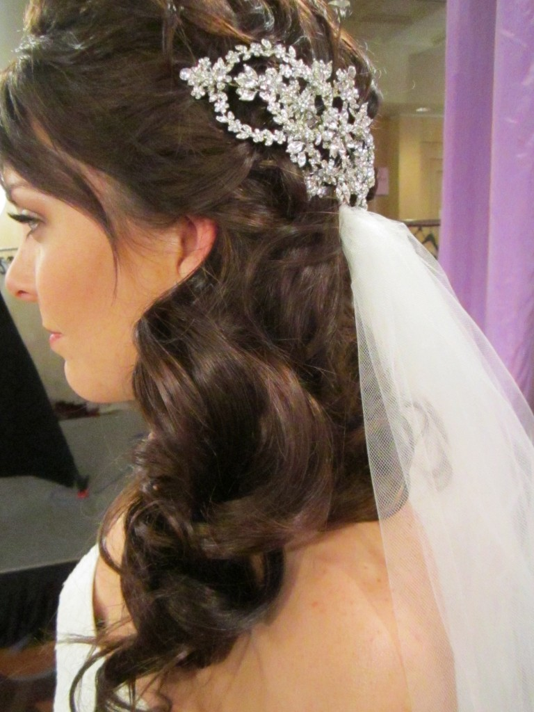 Using hair extensions placed to one side, Lindsay created a soft romantic look with this half up, half down style.  A Malis Henderson headpiece was placed slightly off center to create a focal point and a ton of sparkle!
